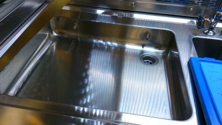 Vista de zona de tallado sin rejilla, se observa cubeta de recepción de líquidos con desagüe y eyectores de limpieza por cortinilla de agua para arrastre de restos de formol.
